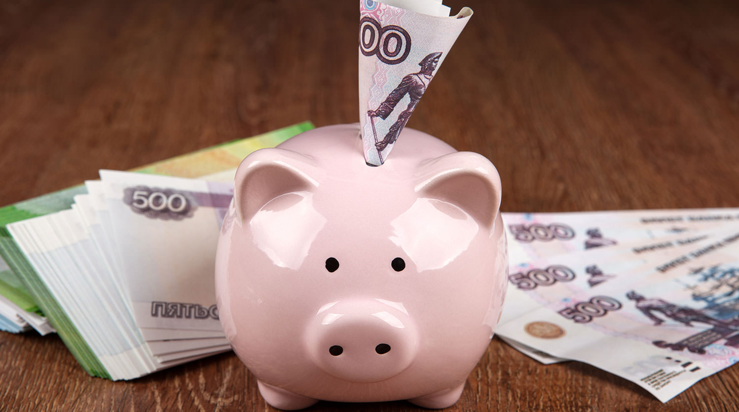 Pink piggy bank with russian banknotes and one banknote in goal